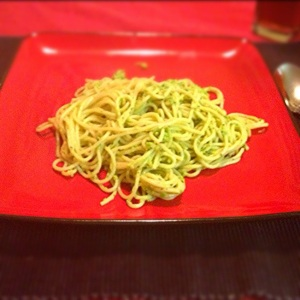 Avocado pasta on a red plate.