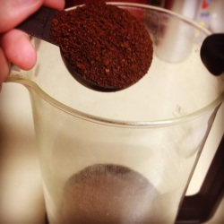 A photo of ground coffee being poured into a french press pot.