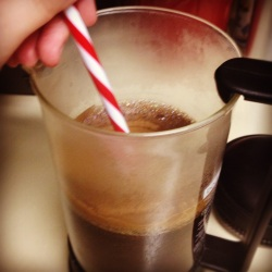 Photo of stirring coffee in a french press.